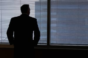 En man i kostym som funderar vid ett fönster